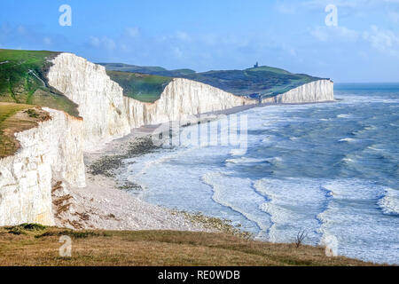 Seven Sisters cliffs, tall white chalk cliffs with the sea infront and on top of the cliffs is grass above a blue sky, at the bottom of the nearest cl - Stock Image