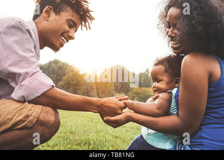 Happy African family enjoying time together in public park - Mother and father having fun  playing with their daughter at sunset outdoor - Stock Image