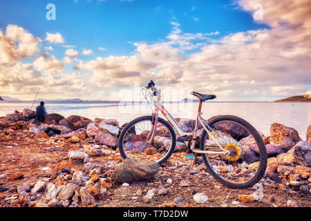 Old rusty bicycle parked on the seashore and an angler fisherman fishing near the sea - Stock Image