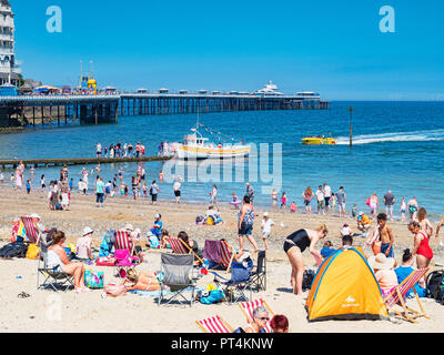 26 July 2018: Llandudno, Conwy, UK - Holidaymakers throng the beach and pier on one of the hottest days of the year, with bright sunshine and clear... - Stock Image