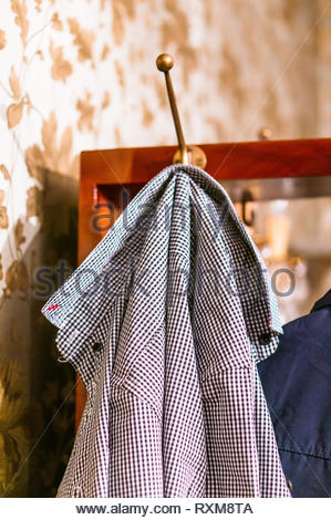 Elegant shirt with small blue and white squares hanging on a hook. - Stock Image