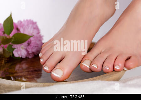 Girl feet with white french manicure on wooden bowl with pink decorative flower and towel in beauty and spa studio. Pedicure and feet health concept - Stock Image