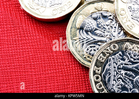 New shiny UK Pound Coin currency of silver and gold on a red background. Coins are designed to stop forgery of the - Stock Image