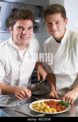 Portrait Of Chef Instructing Trainee In Restaurant Kitchen - Stock Image