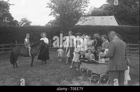 1948, mothers with their children at a garden fete, with a little boy sitting on a pony, England, UK. - Stock Image