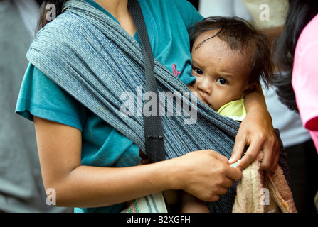 A Mangyan child breast feeds as his mother waits in line to buy rationed rice in Mansalay, Oriental Mindoro, Philippines. - Stock Image