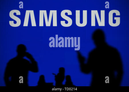 The Samsung logo is seen on an LED screen in the background while a silhouetted person uses a smartphone in the foreground (Editorial use only) - Stock Image