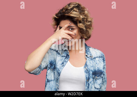 Portrait of funny young woman with curly hairstyle in casual blue shirt standing, covering her eyes and looking through fingers. spy or shy concept. i - Stock Image
