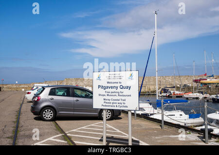 Free parking sign with cars parked by harbour on Pitgaveny Quay, Lossiemouth, Moray, Scotland, UK, Britain - Stock Image
