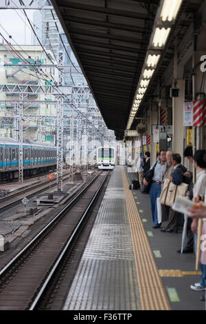 platform with green white train in distance Tokyo Japan - Stock Image