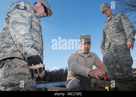 U.S. Air Force Tech. Sgt. Jeremy Carnahan, 20th Civil Engineer Squadron (CES) pavements and equipment journeyman, left, and Airman Zackery Simmons, 20th CES structural apprentice, right, listen as Senior Airman Daniel Nava, 20th CES structures journeyman, explains what cuts they need to make to begin building a bridge at Shaw Air Force Base, S.C., Feb. 5, 2018. The Airmen volunteered to rebuild the overflow bridge at Memorial Lake, which helps channel excess water into storm drains. (U.S. Air Force photo by Senior Airman Destinee Sweeney) - Stock Image