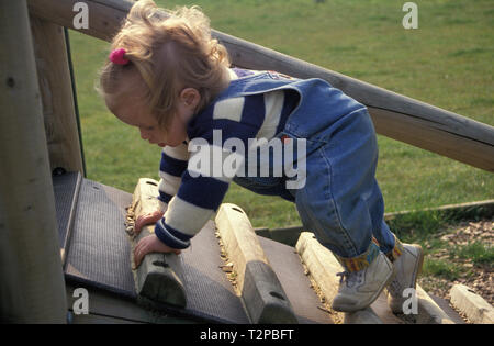 toddler climbing steps in playground on all fours - Stock Image