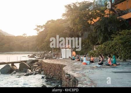 Group of multiple adults meditating outdoors. Yoga retreat Puerto Vallarta - Mismaloya, Mexico - Stock Image