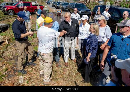 Panama City, Florida, USA. 15th Oct 2018. U.S President Donald Trump greets local residents during a tour of damage in the aftermath of Hurricane Michael October 15, 2018 in Lynn Haven, Florida. Standing with the president from left to right are: FEMA Administrator Brock Long, Florida Gov. Rick Scott, President Donald Trump, First Lady Melania Trump, First Lady of Florida Ann Scott and Homeland Security Secretary Kirstjen Nielsen. Credit: Planetpix/Alamy Live News - Stock Image