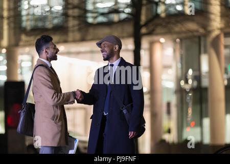 Businessmen handshaking on urban street at night - Stock Image