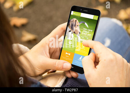 mobile design concept: woman holding a 3d generated smartphone with pet on the screen. Graphics on screen are made up. - Stock Image