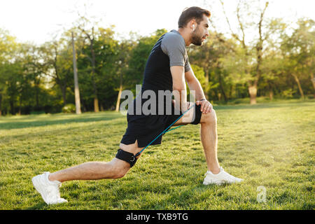 Image of a handsome young strong sports man posing outdoors at the nature park location make exercises with fitness equipment. - Stock Image