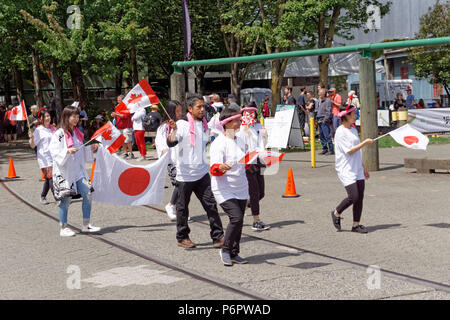 Vancouver, Canada.1st July, 2018. Japanese Canadians wave flags in the annual Canada Day Parade on Granville Island, Vancouver, British Columbia. This year Canada Day celebrates the country's 151st birthday. Credit: John Mitchell/Alamy Live News - Stock Image