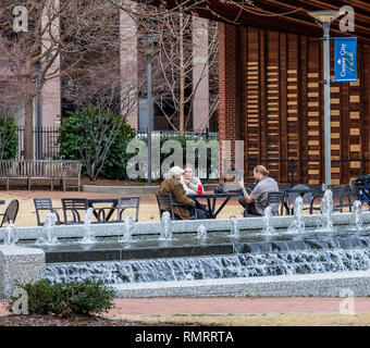 GREENSBORO, NC, USA-2/14/19: A video being made of a discussion between two men, taking place in Center City Park. - Stock Image
