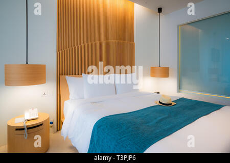 Modern bedroom. Beautiful interior of hotel, apartment with double bed - Stock Image