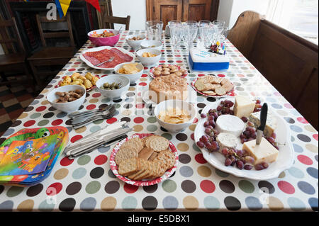 Colorful party table laid out with finger food nibbles and cakes - Stock Image