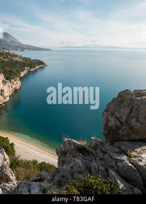 Rocky coastline with view at small hidden beach and blue sea in Croatia on sunny summer day - Stock Image