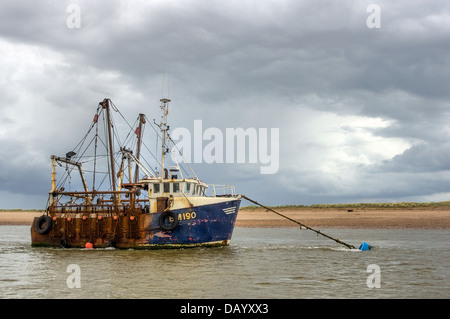 'Marina' (BM190) fishing vessel, alongside the Dawlish Warren sand spit in the Exe Estuary - below a retreating - Stock Image