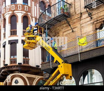 Three men on a Houlotte HA 16 PX boom hoist repairing a metal balcony in Seville, Spain - Stock Image