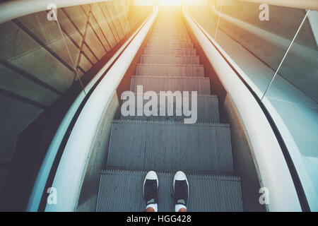 Outdoor city escalator stairway down, feet of guy in gumshoes ready to go down; evening sun, with tiled concrete - Stock Image