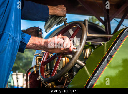 Steam traction engine being driven by a man  surrounded by dirty smoke. - Stock Image