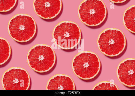 Colorful fruit pattern of fresh grapefruit slices on pink background. Minimal flat lay concept. - Stock Image