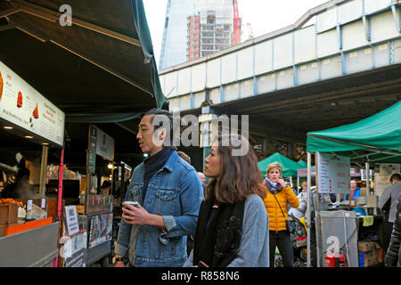 A young couple checking out a food stall at Borough Market in London England UK  KATHY DEWITT - Stock Image