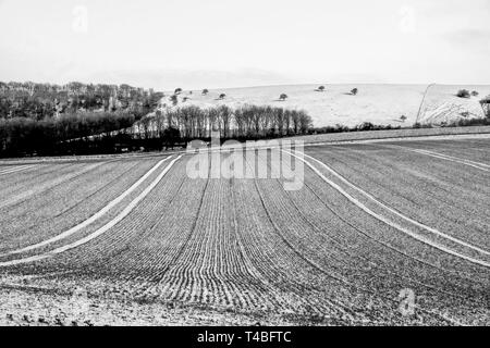 A black and white photograph of freshly ploughed field covered in a thin layer of white frost forming vertical lines, the field is on a hill and behin - Stock Image