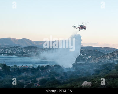 Fire emergency services helicopter spraying water preventing the fire from spreading further on the mountains. Saronida, East Attica, Greece, Europe. - Stock Image