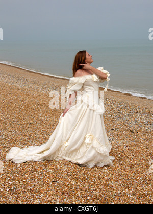 Girl Wearing a Cream White Wedding Dress on a Shingle Beach by the Sea. - Stock Image