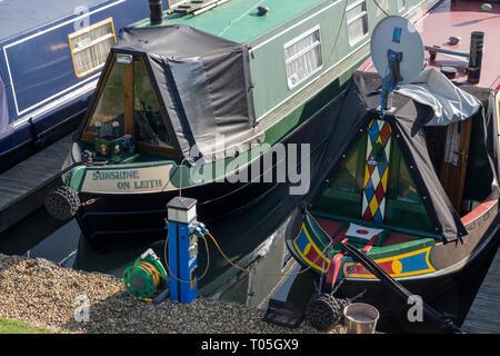 Colourful narrowboats, one bearing the name 'Sunshine On Leith', moored at Blisworth Marina, Northamptonshire, UK - Stock Image