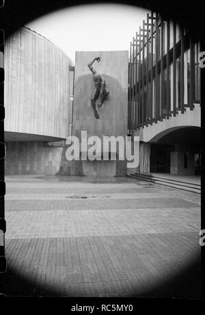 'River God', Civic Centre, Great North Road, Newcastle Upon Tyne, c1955-c1980. A detailed view of the bronze sculpture by David Wynne, hung on the south-facing wall that joins the ellpitical chamber with the west front, seen from the south. The Civic Centre was built by architect George Kenyon, and in stages, with the four storey blocks completed 1958, the 12 storey block 1960-1963, and the council suite completed 1965. The structure is mostly concrete, with some Portland stone ashlar on the facade, as well as granite and hand made Broughton Moor stone bricks. The large bronze sculpture of the - Stock Image