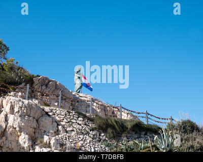 Editorial - Monument of Saint Peter and Croatian flag in Makarska city harbor on sunny day - Stock Image