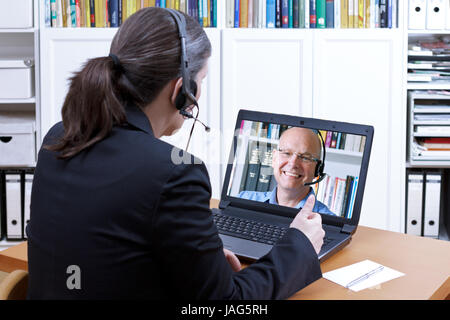 Female attorney-at-law with headset in front of a laptop on her desk giving online advice to an elderly client, - Stock Image