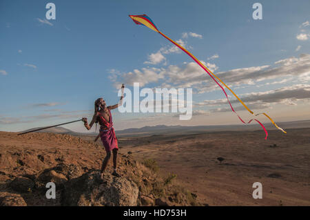 A Maasai Warrior flies a kite over a valley with scenic background. - Stock Image