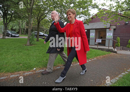 SNP leader Nicola Sturgeon and chief executive of the SNP Peter Murrell leave a polling station at Broomhouse Park Community Hall in Edinburgh after casting their votes for the European Parliament elections. - Stock Image