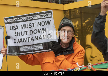 London, UK. 10th December 2018. A protester holds up a poster at the final 'Shut Guantanamo!' monthly protest of 2018 at the US Embassy on the 70th anniversary of the Universal Declaration of Human Rights (UDHR). This declared 'No one shall be subjected to torture or to cruel, inhuman or degrading treatment or punishment' and 'No one shall be subjected to arbitrary arrest, detention or exile.' Guantanamo still has 40 detainees who have been tortured and held in indefinite detention without trial for almost 17 years. Credit: Peter Marshall/Alamy Live News - Stock Image