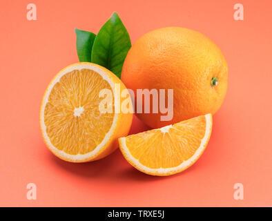 Orange fruit with orange slices and leaves isolated on orange background. - Stock Image