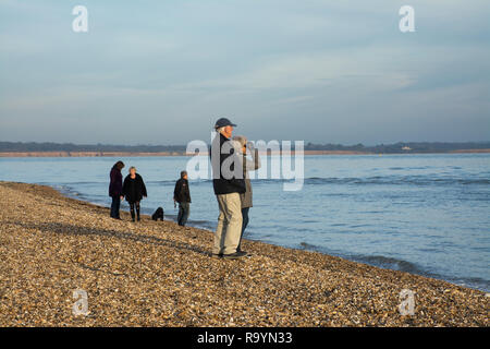 People enjoying a winter walk on the beach in Hampshire, UK. Leisure, visitors, dog walkers, looking out to sea - Stock Image