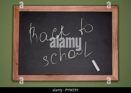 Back to school written on chalk board with wooden frame on green background - Stock Image