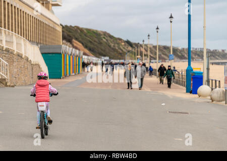 Bournemouth, Dorset, UK. 12th January 2019. Young girl rides a bike along the promenade in Boscombe, Bournemouth. Credit: Thomas Faull/Alamy Live News - Stock Image
