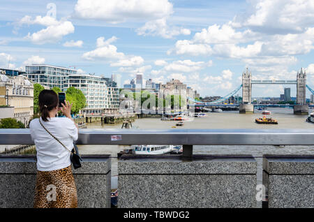 A lady on London Bridge takes a photograph of Tower Bridge at The River Thames using her mobile phone. - Stock Image