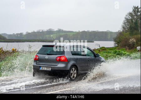 Skibbereen, West Cork, Ireland. 15th Apr, 2019. Much of Ireland is currently in the midst of a Status Orange Rainfall Warning, issued by Met Éireann. A car negotiates a spot flood on the N71 near Skibbereen. Credit: Andy Gibson/Alamy Live News - Stock Image