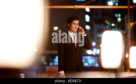 Smiling businessman talking on cellphone against night view of city - Stock Image
