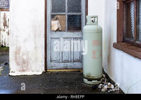 Large domestic gas bottle outside cottage on Valentia Island, county Kerry Ireland - Stock Image